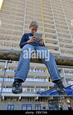 boy playing with gameboy in front of tower block, Germany, Chorweiler , Cologne - Stock Photo