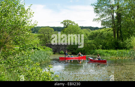 People in two bright red canoes paddling on lake surrounded by emerald vegetation & tall trees, National Botanic - Stock Photo