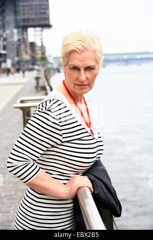attractive white-haired woman at a Rhine promenade casually carrying her jacket over an arm, Germany, North Rhine - Stock Photo