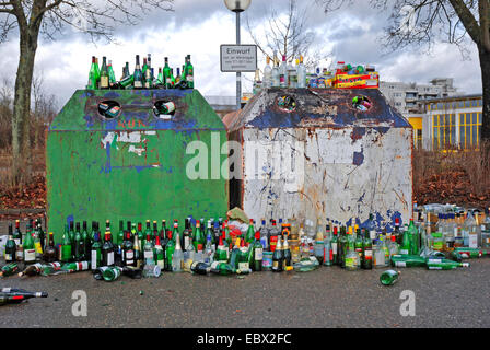 empty bottles around a abuzzed bottle bank, Germany - Stock Photo
