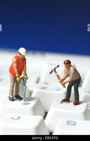 Construction workers on computer-keyboard - Stock Photo
