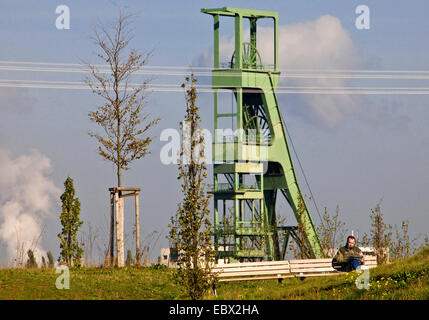 a man sitting on a bench in front of a headgear reading a newspaper, Germany, North Rhine-Westphalia, Ruhr Area, - Stock Photo