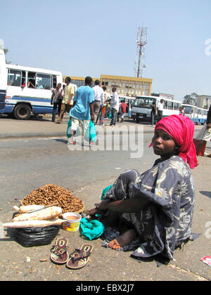 street scene in the capital city; young woman on the ground selling cassava and peanuts to passengers at the central bus station near the market, Burundi, Bujumbura marie, Bujumbura
