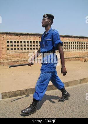 police officer with baton patrolling on a large street of the capital city, Burundi, Bujumbura marie, Rohero 1, - Stock Photo