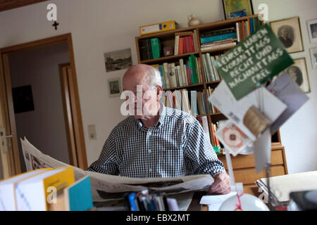 elderly man reading newspaper at his desk, postcard labeled with 'teachers have been right in the morning and free - Stock Photo