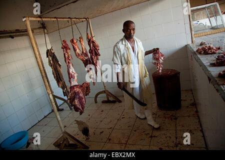 butcher cutting meat on a log of wood, Rwanda, Nyamirambo, Kigali - Stock Photo