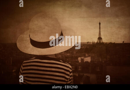 Back view of little girl with hat watching Paris skyline. Dark and moody setting. - Stock Photo