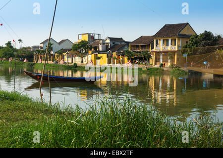 River scene of Hoi An in Vietnam with traditional fishing boat. - Stock Photo