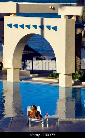 young woman taking a sunbath at the swiming pool of a luxurious hotel, Tunisia, Djerba - Stock Photo