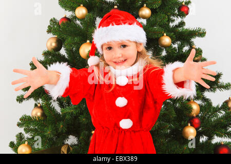 little girl dressed up as Santa Claus with a christmas tree, Switzerland - Stock Photo