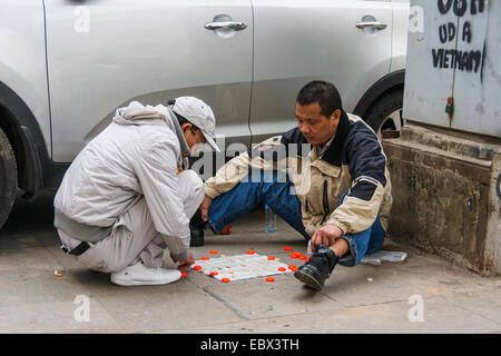 Two Vietnamese men playing checkers in the street in Hanoi - Stock Photo