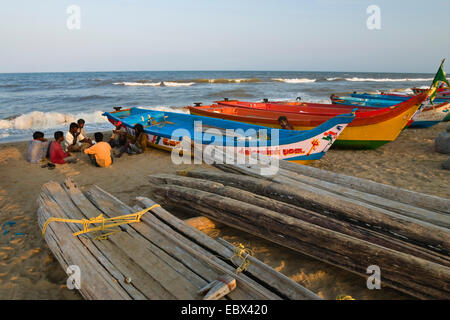 fishermen sitting on sand beach beside their boats, India, Tamil Nadu, Marina Beach, Chennai - Stock Photo