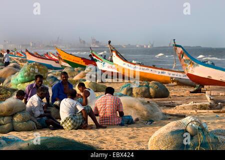 fishermen sitting on sand beach among their boats and nets, India, Tamil Nadu, Marina Beach, Chennai - Stock Photo