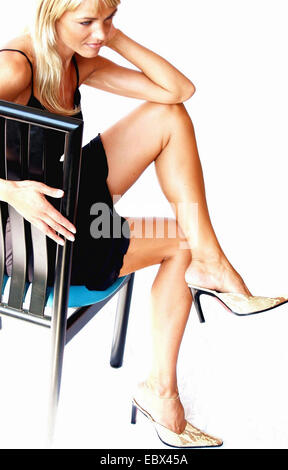 blond young woman sitting on a chair in a tight cloth and high heels with crossed legs - Stock Photo