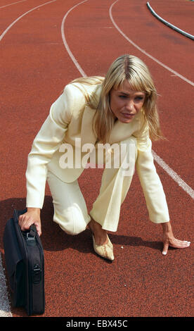 business woman in a trouser suit with a brirfcase in the starting position on a tartan track in a sports stadium - Stock Photo