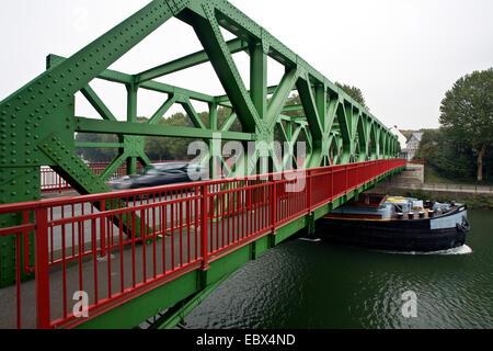 cargo ship on Dortmund Ems canal, a car passing the Lucas bridge, Germany, North Rhine-Westphalia, Ruhr Area, Datteln - Stock Photo