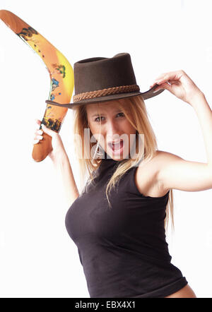 long-haired blond young woman wearing a wide-brimmed black hat and top is reaching back for throwing a boomerang - Stock Photo