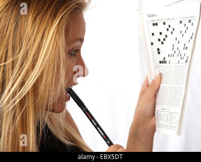 hand holding a pen and solving a crossword puzzle Stock