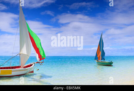 two traditional colorful Mauritian pirogues (flat wooden boats) in the water close to the beach, Mauritius - Stock Photo