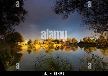 sun shining on a lake shore through a hole in a cloud cover, Germany, Lower Saxony, Vogtlaendische Schweiz, Dorum - Stock Photo