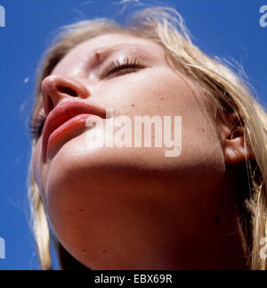 portrait from below of a blond young woman taking a sunbath - Stock Photo