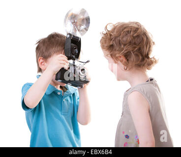 Young Photographer. Two small kids playing with antique camera - Stock Photo