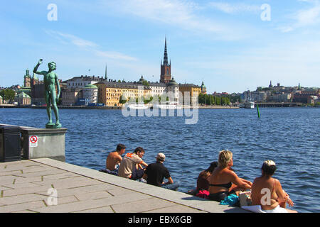 Gamla Stan with view at the Riddarholmen Church and Stadshuset park statue the singer, Sweden, Stockholm - Stock Photo