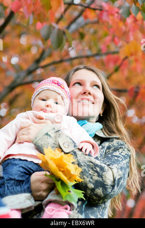 Young mother with daughter enjoying beautiful autumn day - Stock Photo
