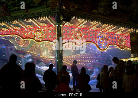 persons in front of an illuminated carrousel by darkness, Germany, Berlin - Stock Photo