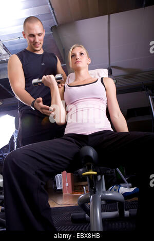 Young woman training with dumbbells with help of a trainer - Stock Photo