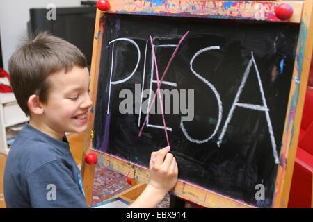 Symbol related to the Pisa study, child correcting PIESA - Stock Photo