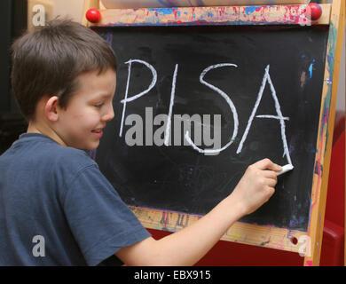 Symbol related to the Pisa study, child writing PISA - Stock Photo