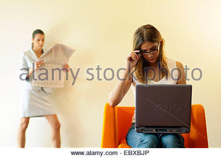 woman sitting in a chair, working with laptop, another woman reading the newspaper - Stock Photo