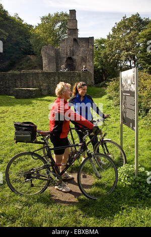 young couple on bicycles reading a infromation sign at Hardenstein Castle ruin, Germany, North Rhine-Westphalia, - Stock Photo