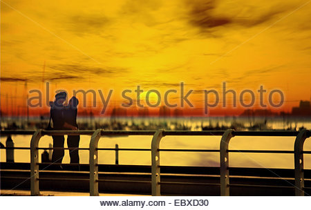 sunset and couple in love in foreground, hugging - Stock Photo