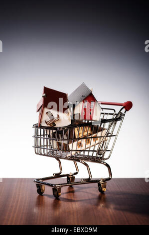 Three models of houses are stacked in a shopping cart. - Stock Photo