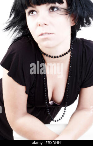 young black-haired woman with black necklace in a black top with deep cleavage - Stock Photo