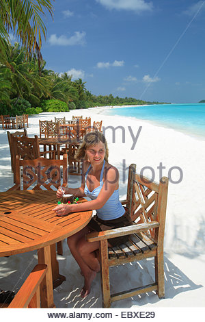 young woman sitting in a bar at the beach, enjoying a cocktail, Maldives, Indian Ocean - Stock Photo