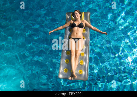 young woman on air mattress in a swimming pool, Austria - Stock Photo