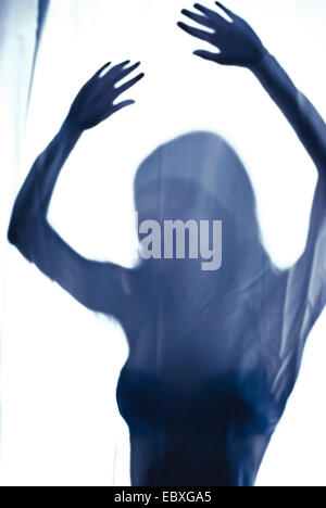 young woman behind curtain - Stock Photo