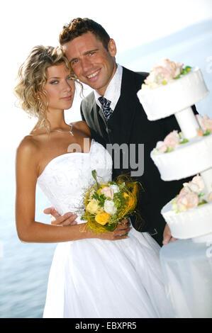 pridal couple outside, with weddingcake - Stock Photo