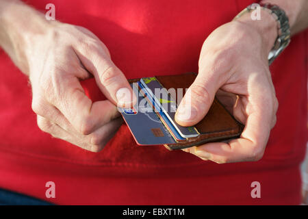 A man in a red top removing a Nationwide bank credit card from a wallet to pay for a purchase. England, UK, Britain - Stock Photo