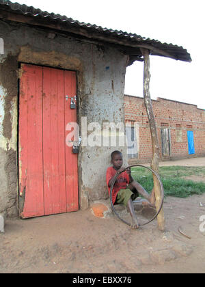 boy sitting next to the closed door of a small shop with an old bicycle tyre in hands, Uganda, Gulu, Gulu - Stock Photo