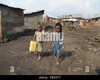 children fetching water with canisters in a poor part of the city of Goma, being called the 'burned quarter' ('quartier - Stock Photo