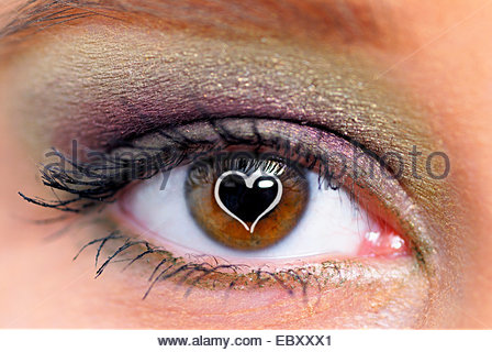 heart on the pupil of a young woman's eye symbolising 'amorousness' - Stock Photo