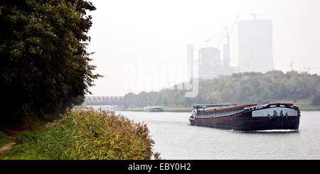 cargo ship on Dortmund Ems canal mit coal-fired power station Datteln 4 of E.ON AG in the background, Germany, North - Stock Photo