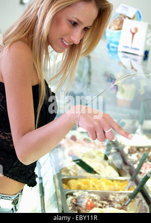 blond young woman in an ice cream parlor chosing the sorts with a smile - Stock Photo