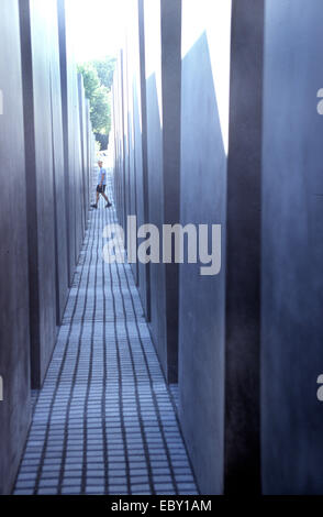view through a corridor of the holocaust memorial at a walking young man, Germany, Berlin - Stock Photo