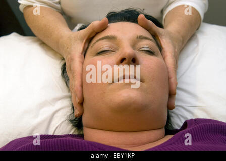 Young woman having a Reiki session at an indoor Christmas market, near Alton, Hampshire, UK. - Stock Photo