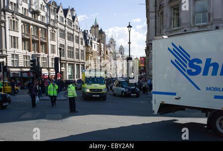 A London ambulance is helped through traffic by Police near Trafalgar square - Stock Photo
